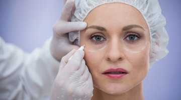 doctor-marking-female-patients-face-for-cosmetic-treatment